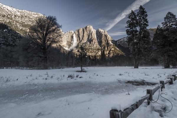 Yosemite Falls illuminated by sun, viewed from across a field | LotsaSmiles Photograhy